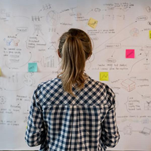 Woman in front of whiteboard covered with notes