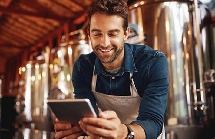 Man in apron smiling at tablet with brewery equipment behind him