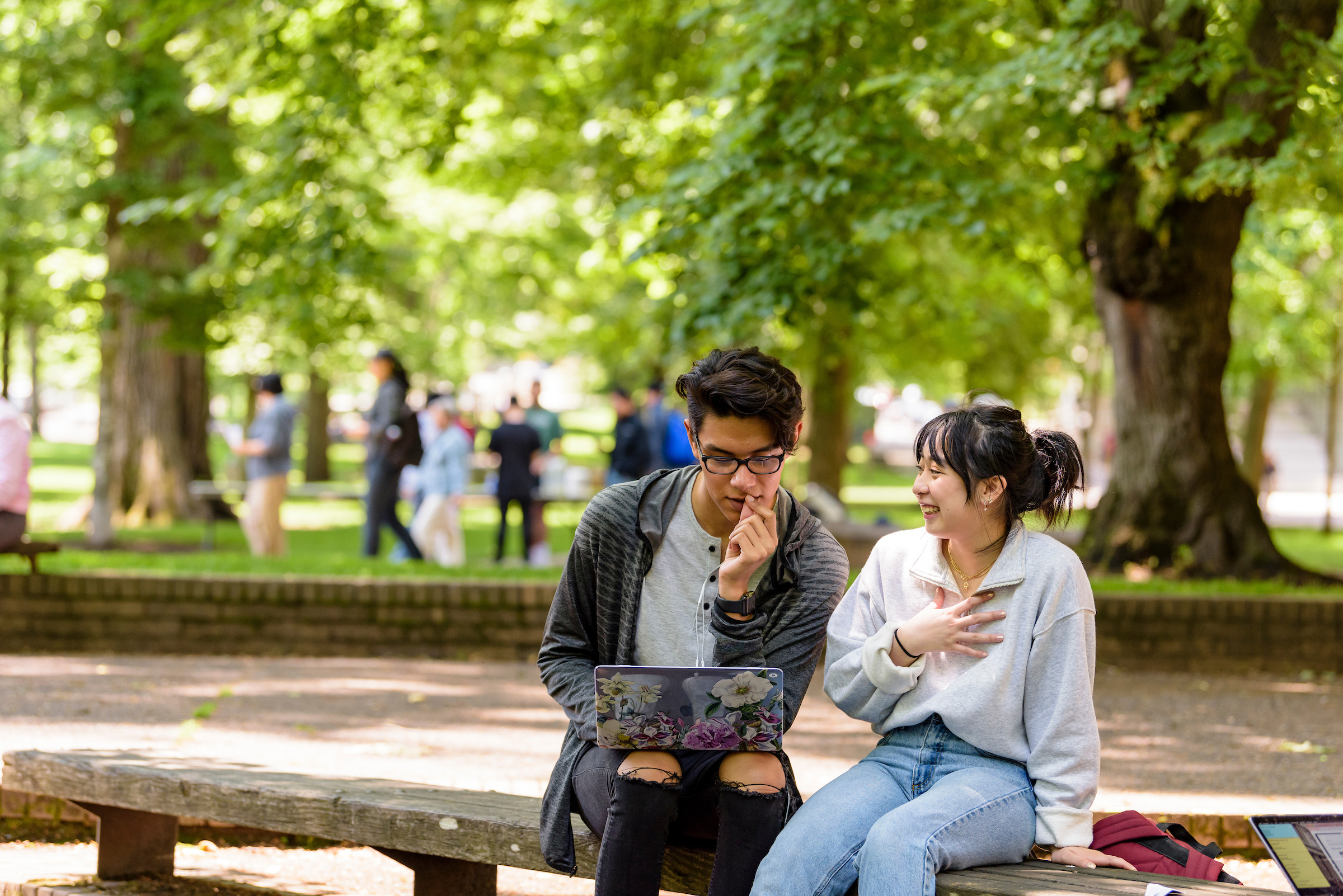 Two PSU Online students working on a laptop in a park