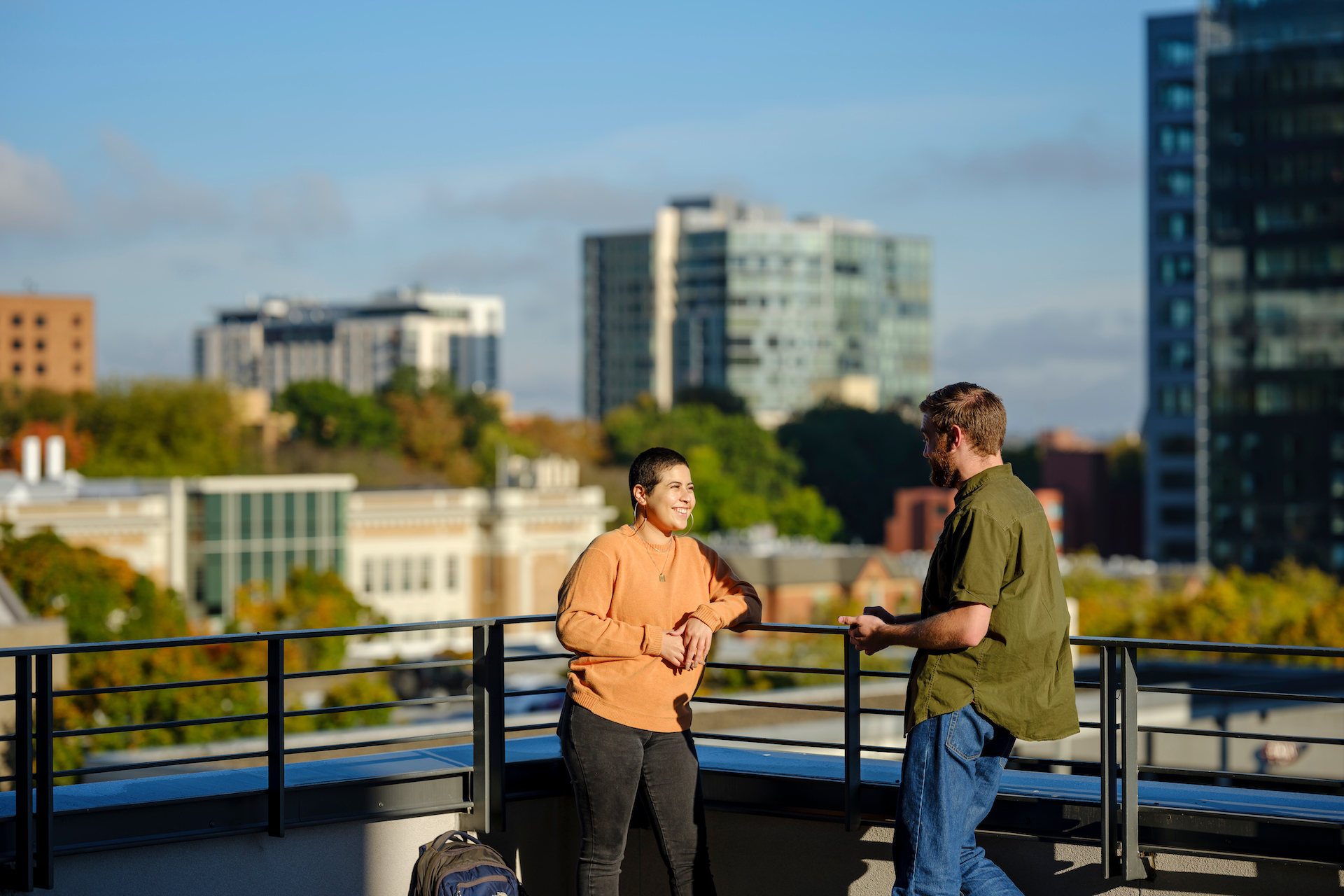 Two psu online students talking on rooftop terrace