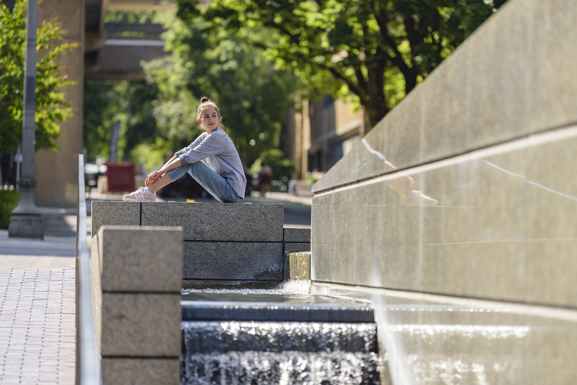 PSU online student sitting by a fountain