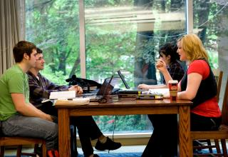 Group of four students studying at library