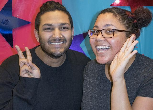 two black and brown queer people smile enthusiastically in front of a pink and blue starry background flashing peace signs