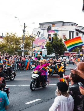 image of a sunny pride parade and dykes on bikes rides down the street