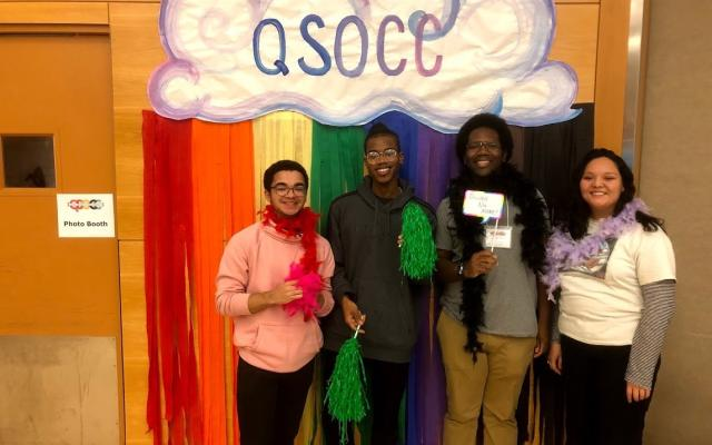 4 QTBIPOC stand in front of a cloudy rainbow QSOCC sign