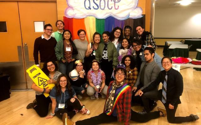 a group of QTBIPOC smile in front of a rainbow QSOCC sign. one is doing the splits, one clutches a wet floor sign jokingly. the mood is silly.