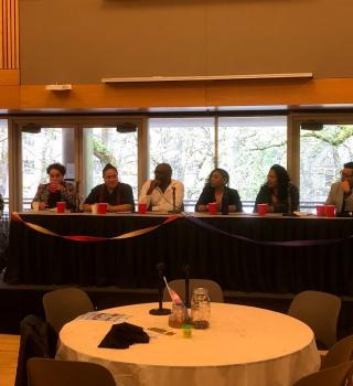 a oanel of QTBIPOC speakers sit on a stage speaking at QSOCC