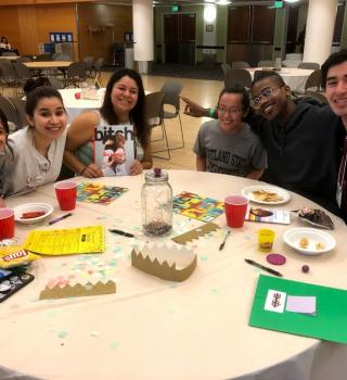 a group of QTBIPOC do crafts around a table with one another and smile with arms around each other