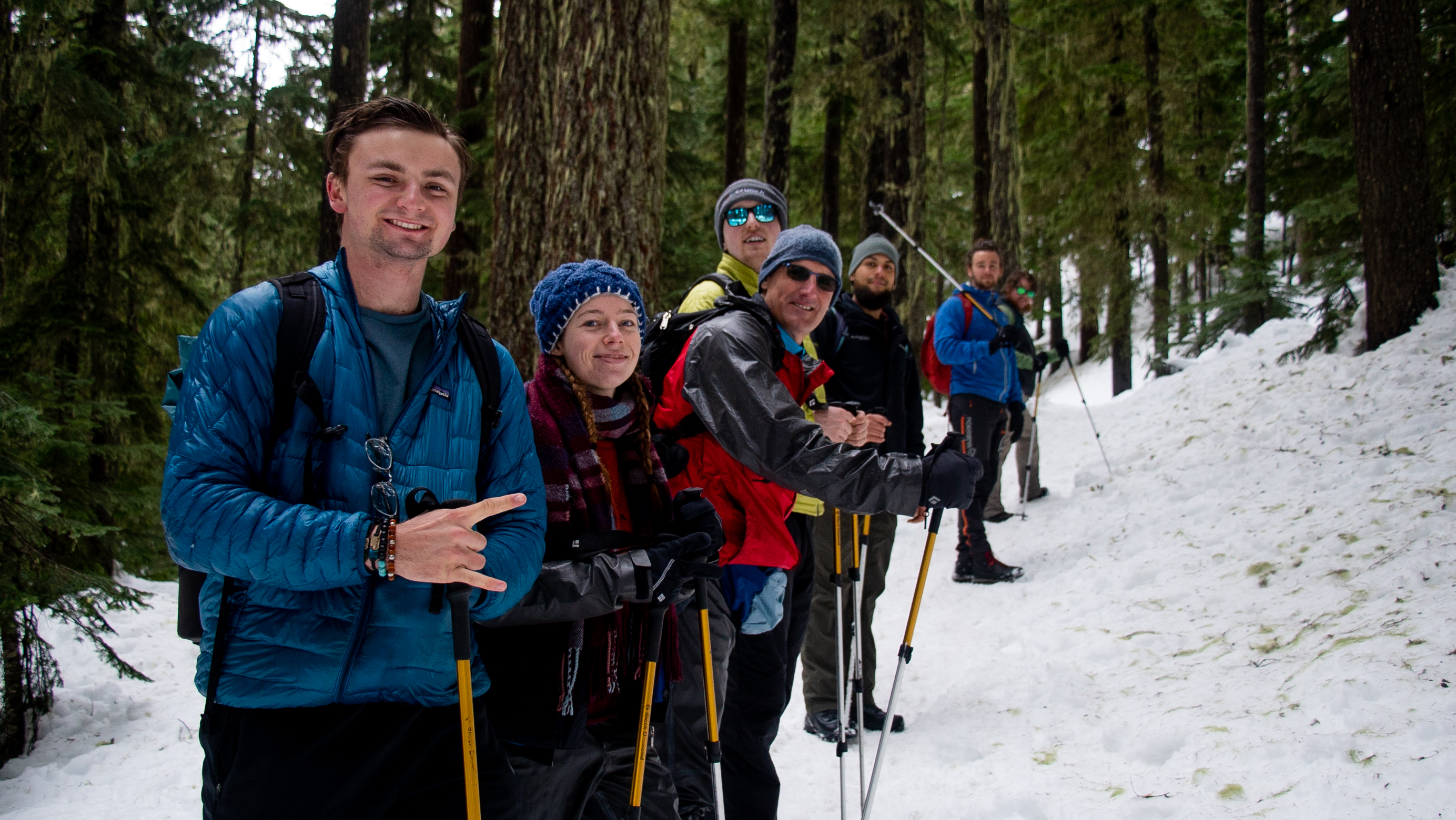A group of people lined up in the snow with snowshoeing equipment.