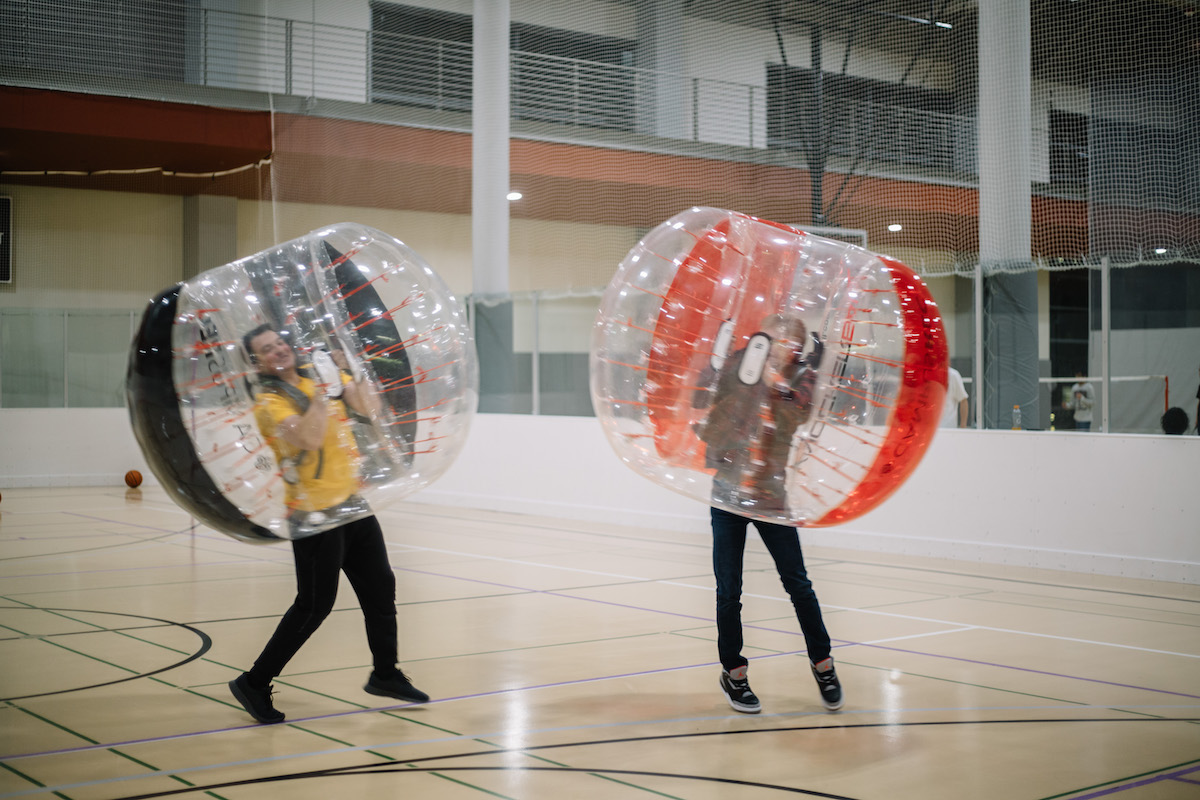 Two people smile while wearing giant inflatable bubbles for bubble sports.
