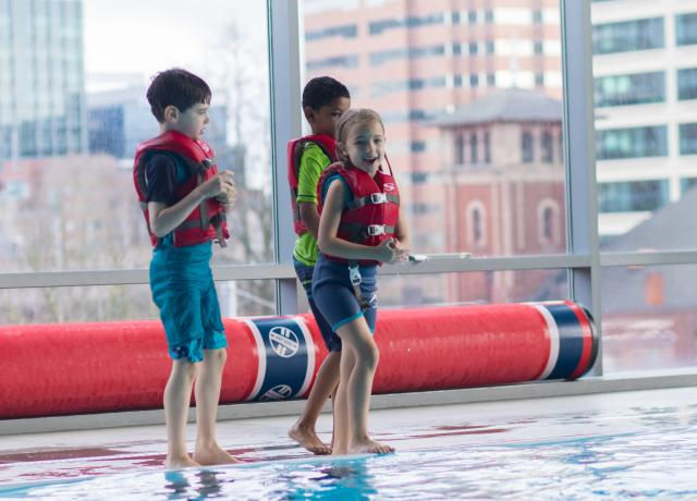 Kids standing by pool in life jackets