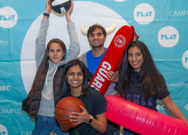 A group of students poses at a photo booth with a volleyball, basketball, inner tube, and lifeguard float at Night at the Rec 2019