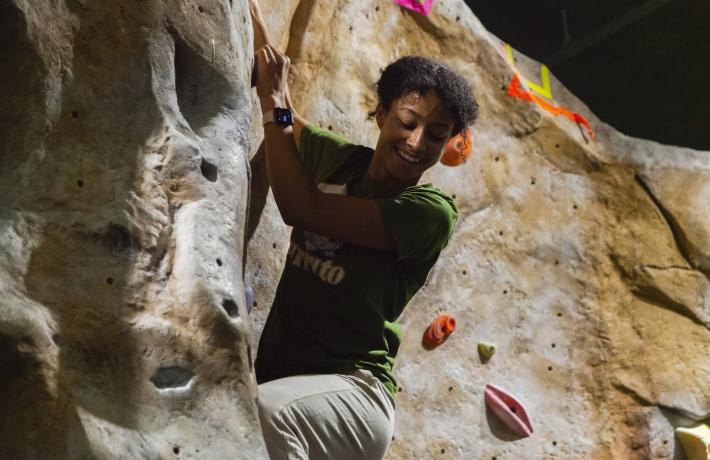 Female person of color smiling and climbing on the Climbing Wall
