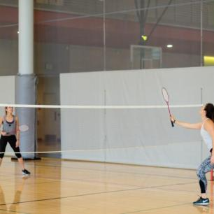 The image is of two people playing badminton in a gym.