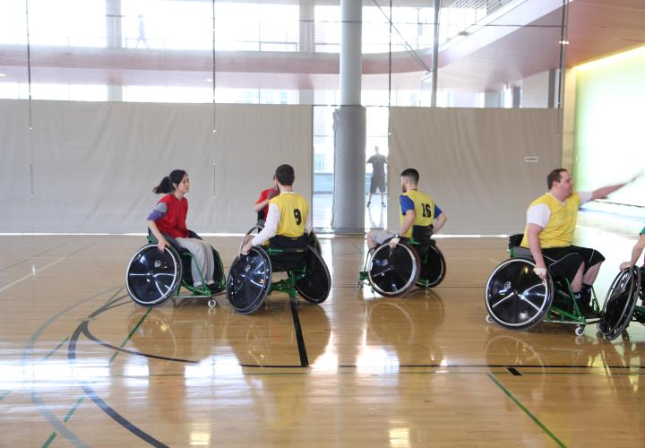 A group of people playing wheelchair basketball in a gym.