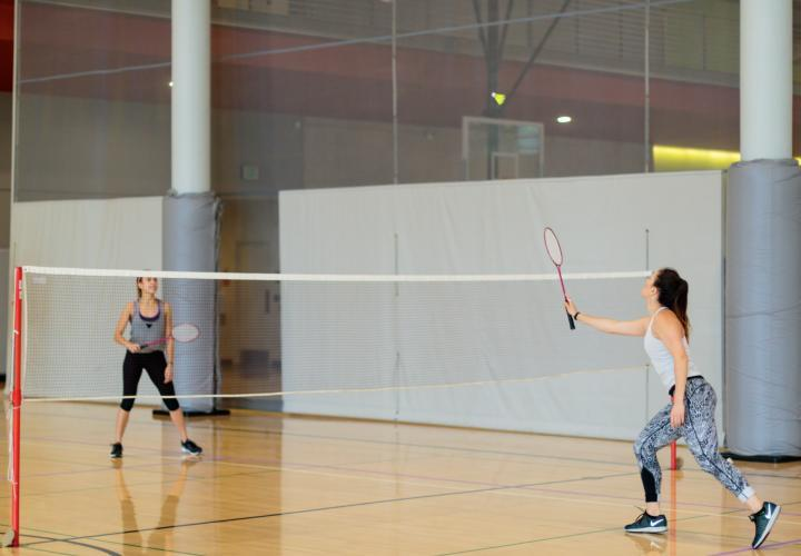 The image is of two people playing badminton together in a gym.