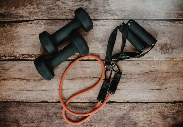 The image is of two black weights and an orange and black jump rope on a wood floor.