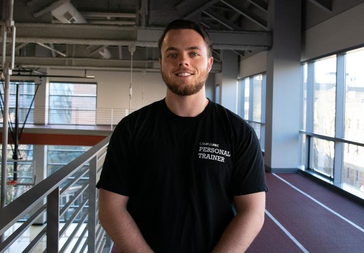 Personal trainer Ben Kirkpatrick stands on the indoor track smiling