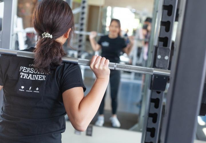 The image is of a person holding a weight bar and looking into a large mirror.