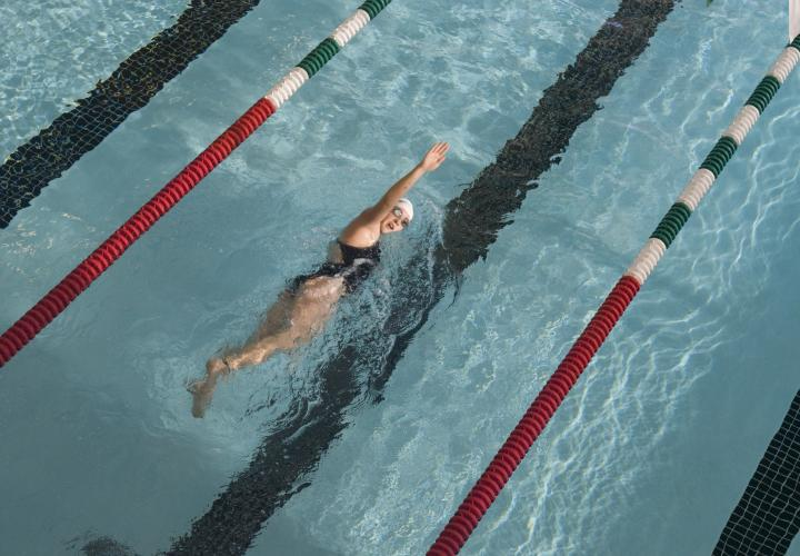 A person swims laps in the Rec Center pool, their arm up in the freestyle position.