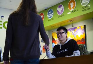 Student scanning ID card at the Membership Services desk.