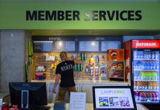 Student wearing a staff shirt standing in front of Member Services sign.
