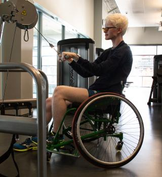 Wheelchair user performing a strength exercise on a machine in the Weight Room.