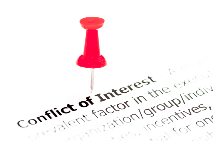 Conflict of interest document with red push pin.