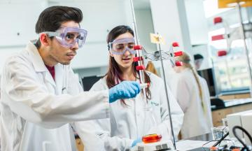 Two students with lab coats and safety glasses working on experiment in chemistry lab