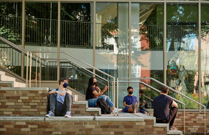 students wearing masks sit outside building