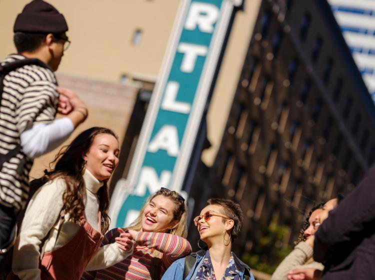 Students hanging out on Broadway in front of the Portland theater sign