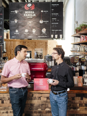 Two people standing in front of a coffee counter talking