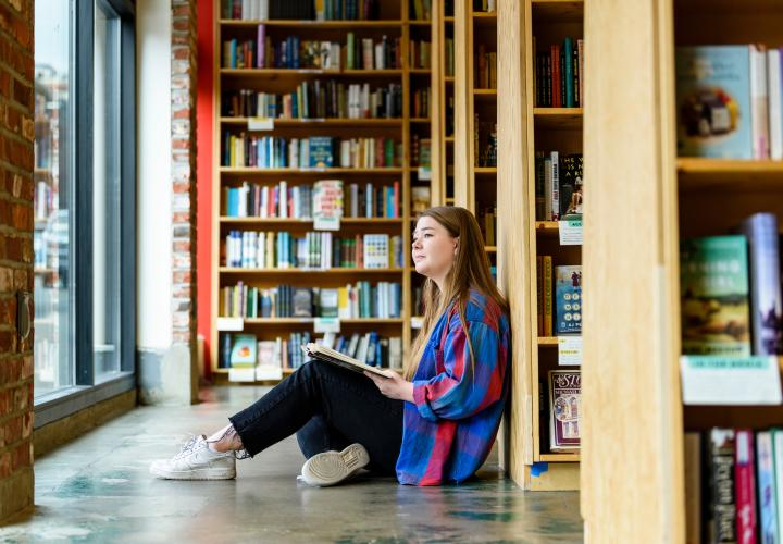 Student on the floor with a book at Powells Books