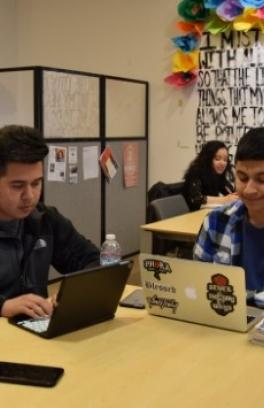 La Casa Latina Student Center with students on computers at a table.