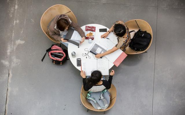 arial view of 3 students around a table studying
