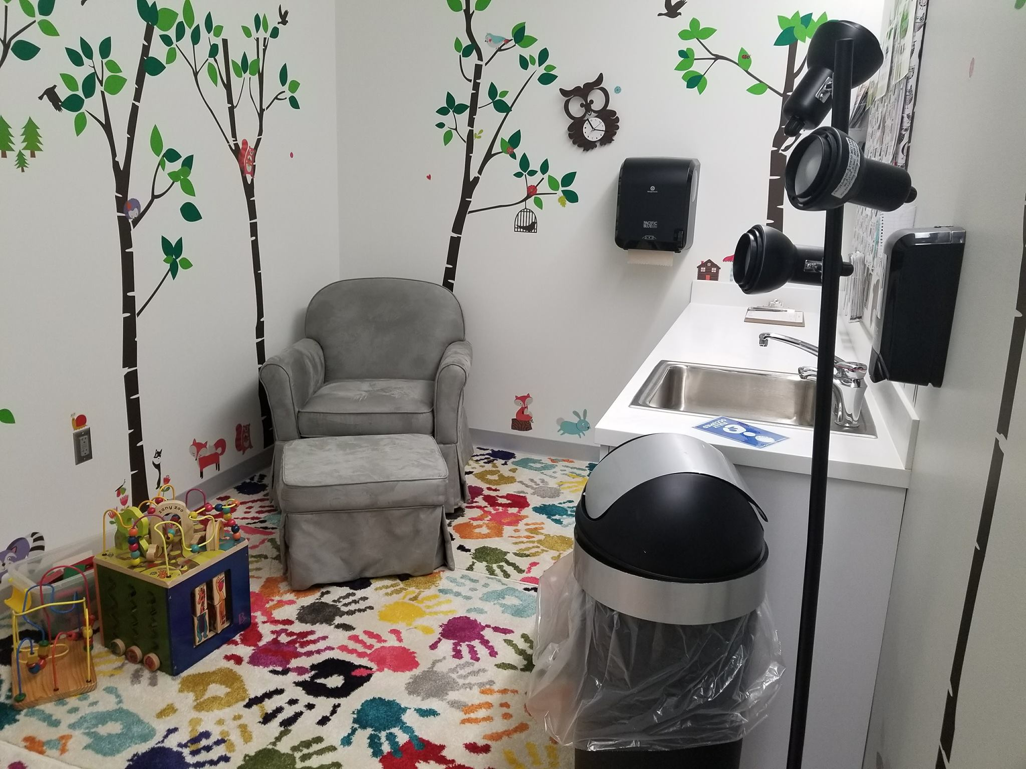 Lactation room equipped with a chair, foot rest, sink, trashcan, and children's toys.