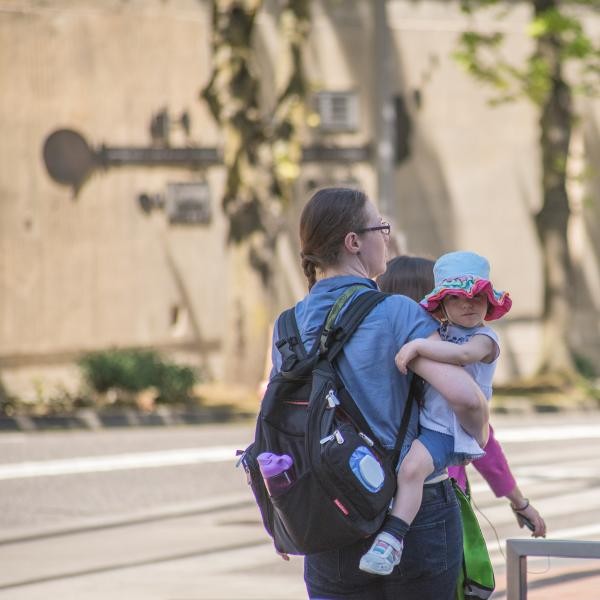 A mother with a backpack on walking outside while holding her young child.