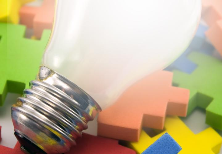 A lightbulb resting on a pile of foam puzzle pieces.
