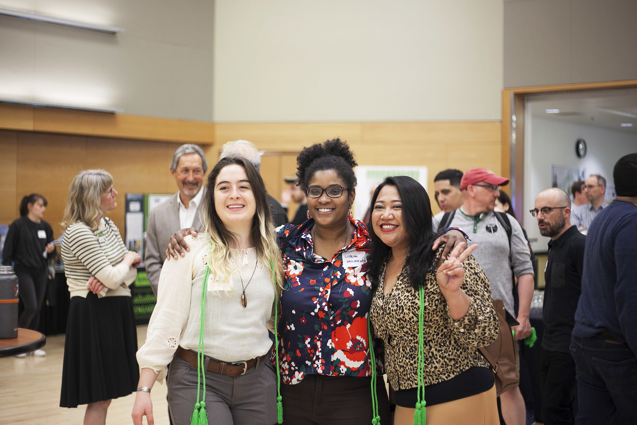 three students with green graduation cords