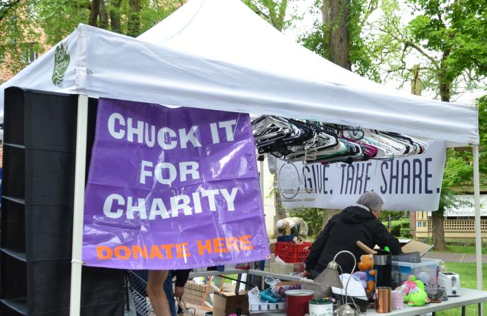 Tent with donated items and sign saying chuck it for charity donate here