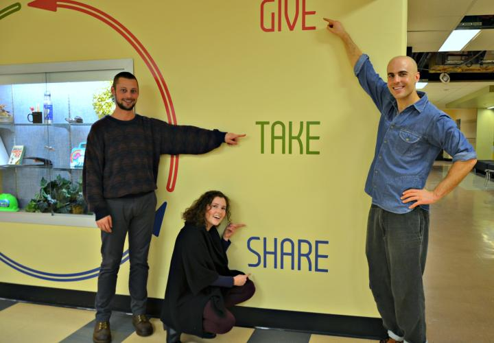 Three people pointing to wall mounted sign saying give take share