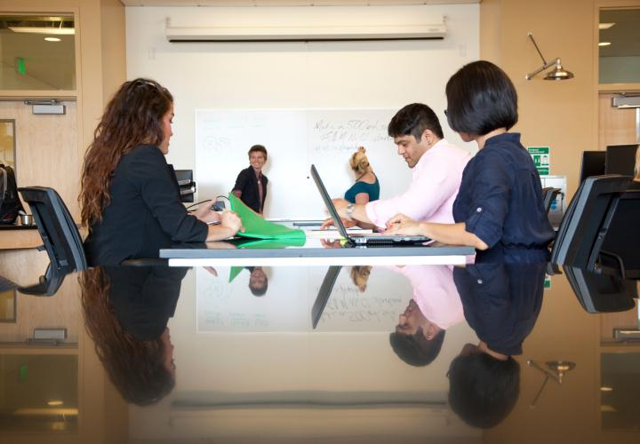 students around table and person writing on white board