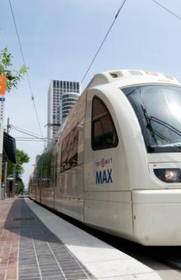 max train near sign that says university district with arrows to destinations