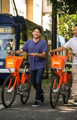 two students walking with orange biketown bike share bicycles