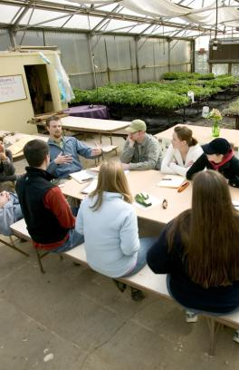 several people sitting around a table with greenhouse plants behind them