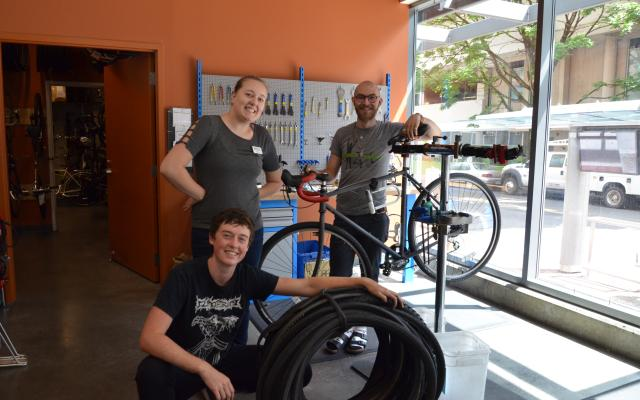 3 people standing with a bike and bike tires