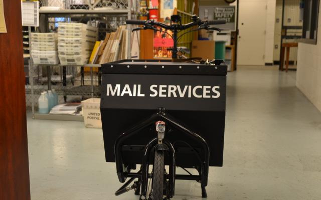 Bike with storage container labeled mail services