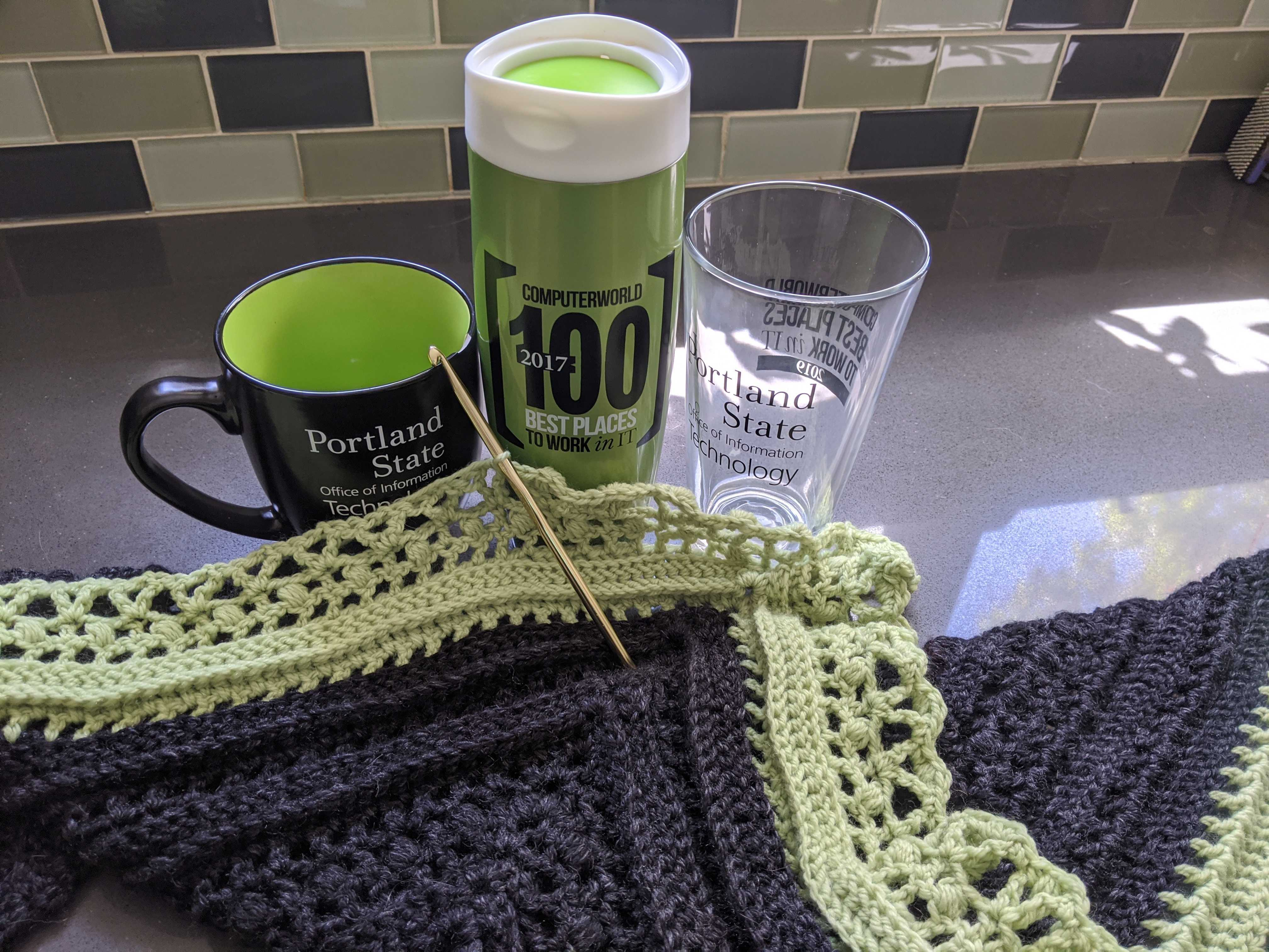 Three mugs celebrating our awards for Best Place to Work in IT, sitting on a countertop next to a shawl crocheted in the PSU colors.