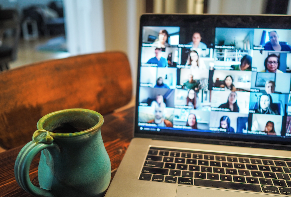 Open laptop on a table with a mug in foreground. A multi-person Zoom meeting is shown on the laptop's screen.