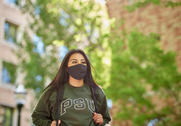 Student wearing mask walking across PSU campus.